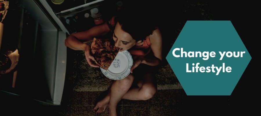 woman eating beside fridge